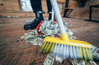 Broom sweeping dollars in scoop from on wooden floor