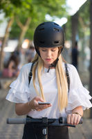 Woman using smartphone and renting modern electric scooter with an application. Urban transport concept