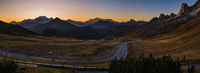 Sun glow in evening hazy sky. Italian Dolomites mountain silhouettes panoramic peaceful view from Giau Pass. Climate
