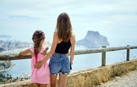 Rear view mother hug daughter family traveling around Spain admiring view of Penyal d'Ifac Natural Park of Calpe, picturesque nature warm sunny summer day. Travel and tourism concept