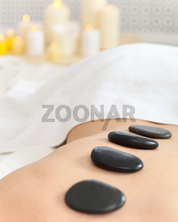Closeup of young woman receiving hot stone massage