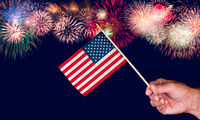 Senior man hand holding a small USA flag against fireworks background