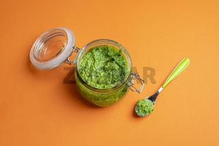 Pesto sauce in an open jar. Eating pesto dip. Homemade savory dressing