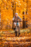 Boy riding bicycle in autumn park