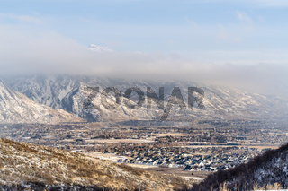 Houses in the suburbs surrounded by striking mountain scenery covered with snow