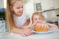 Zwei Kinder naschen von Kuchen in der Küche