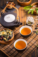 Herbal and fruit tea concept with teapot and infuser and assorted herbal leaves on wooden background