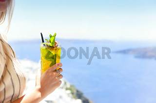 Woman holding a glass of passion fruit cocktail in Santorini background