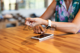 woman using smartphone with smart watch