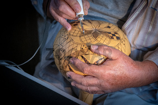 Professional artist maker working in workshop crafting on pumpkin. Creative people handmade crafts