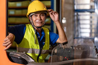 Asian warehouse worker with forklift in warehouse