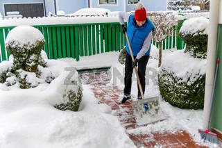 Frau beim Schnee schaufeln