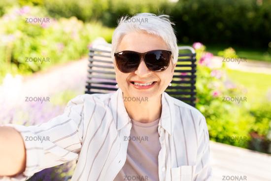 happy senior woman taking selfie at summer garden