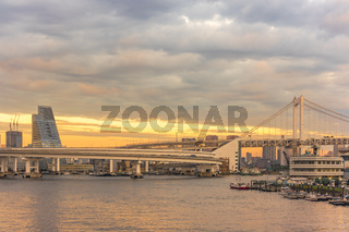 Sunset on circular highway leading to the Rainbow Bridge with Cargo and cruise ships