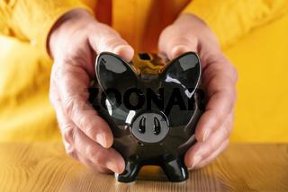 Hände umfassen ein schwarzes Sparschwein