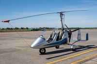 Ein Tragschrauber in der Seitenansicht auf einem Flugfeld mit gesichertem Rotor