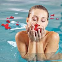 Frau im Schwimmbad mit Rosenblättern