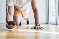 Handsome young man working out at home with a smart watch