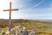 Summit cross on a rocky mountain peak overlooking beautiful autumn landscape in the Swabian Jura