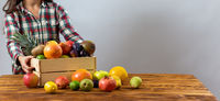 Young lady putting wooden box with fruit on the table