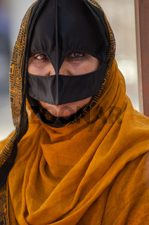 An Omani Bedouin woman wearing a traditional Batoola face covering