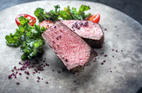 Barbecue dry aged wagyu roast beef natural sliced offered with rapini and tomatos as closeup on a modern design plate