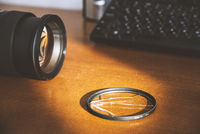 Broken glass of UV filter near the DSLR camera on the photographer work table. Sample of a crushed filter and a saved lens. Theme of protecting an expensive lens from damage. Matte effect