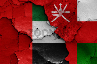 flags of UAE and Oman painted on cracked wall