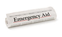 Rolled newspaper with the headline Emergency Aid