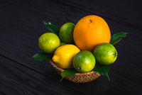 orange, lemon and three limes lie in a rustic plate on a brown table.