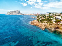 Aerial photo Benissa or Benisa rocky coastline, view to Penyal d'Ifac Natural Park of Calpe resort. Mediterranean Sea turquoise water cloudy sky sunny idyllic summer day. Costa Blanca, Espana, Spain