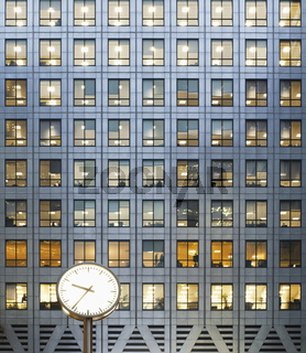 Clock and office windows at dusk