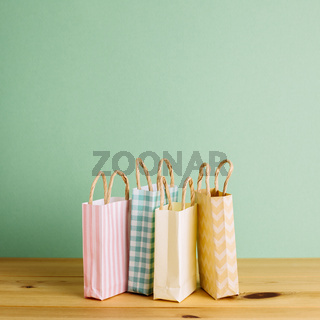 Colorful paper shopping bags on wooden table
