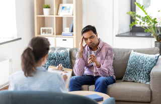 man and psychologist at psychotherapy session