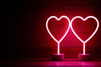 Two glowing pink neon hearts