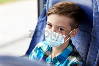 boy in mask sitting in travel bus or train