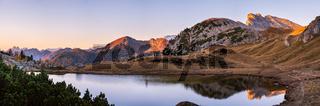 Early morning autumn alpine Dolomites mountain scene. Peaceful Valparola Path and Lake view, Belluno, Italy.