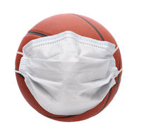 Covid-19 and Sports Concept. A basketball with Surgical Mask, isolated onb white