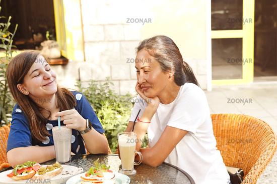Cheerful multiethnic women enjoying lunch in outdoor cafe