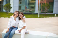 Mother and teen daughter sitting on bench on street