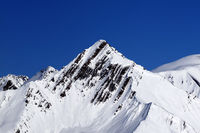 Snowy mountains peak and blue clear sky
