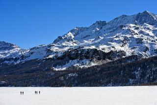 Fussgänger überqueren den zugefrorenen Silsersee, Corvatsch Massiv hinten, Sils im Engadin,Schweiz