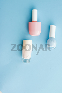 Colourful nail polish bottles on blue background, organic make-up and cosmetic products for beauty brand