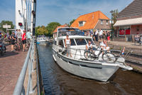 Pedestrians and bikers waiting for opened bridge for passing yachts