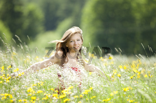 Maedchen tanzt in einer Blumenwiese