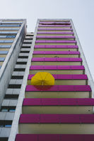 A skyscraper with balconies and a yellow parasol