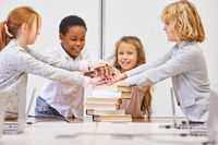 Gruppe Kinder in Grundschule stapeln Hände zur Motivation