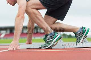 Side view of a man ready to race on running trac