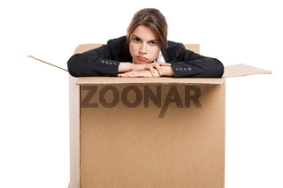 Stressed business woman inside a card box