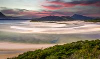 Pink clouds at sunrise over Hill Inlet at Whitsunday Island in rare green color